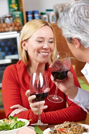 Happy senior couple drinking red wine in a restaurant photo