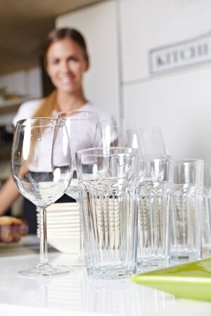 Clean dishes in kitchen with smiling female kitchen staff photo