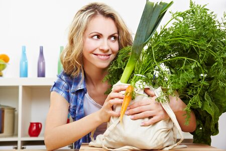 fabric bag: Smiling woman in kitchen with organic vegetables in grocery bag