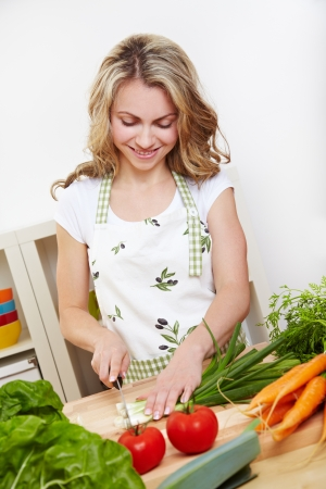 Vegetarian woman in kitchen cutting different vegetables Stock Photo - 14639843