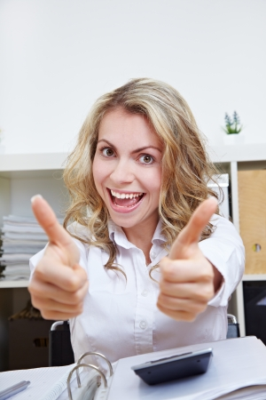 Cheering female student at desk holding both her thumbs up photo