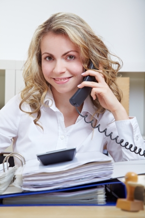 Smiling business secretary on the phone in her office photo