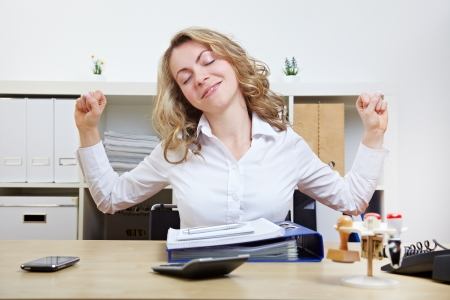 Business woman at her desk stretching her muscles
