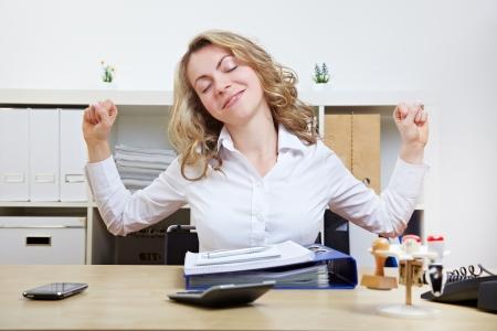 Femme d'affaires � son bureau d'�tirement ses muscles Banque d'images