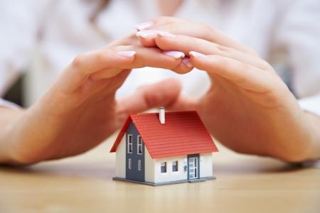 Manos femeninas de ahorro pequeña casa con techo