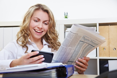 Happy business woman with smartphone reading financial section of newspaper in the office photo
