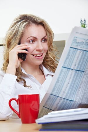 Business woman in office reading a newspaper and making a call with her smartphone photo