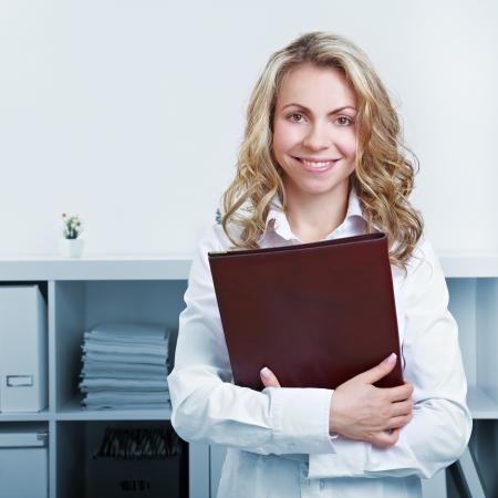 cv: Feliz mujer rubia con CV y ??reanudar en la oficina Foto de archivo