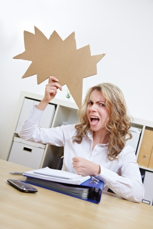 Frustrated woman with empty jagged speech balloon at her desk photo
