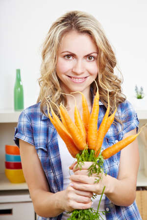 Smiling happy woman in her kitchen with bunch of carrots Stock Photo - 14639880