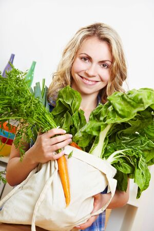 fabric bag: Smiling young woman in kitchen with shopping bag full of vegetables