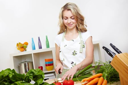 Smiling happy woman cutting green onions and other vegetables in the kitchen Stock Photo - 14736687