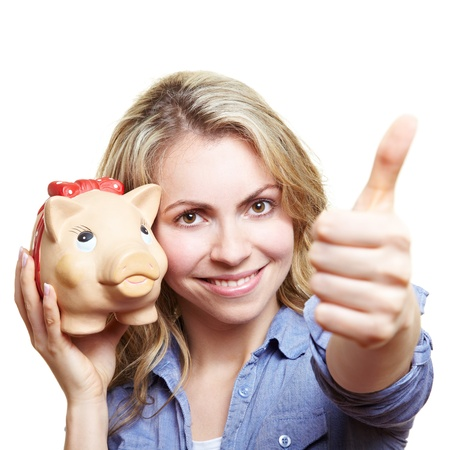 Happy smiling woman with piggy bank holding thumbs up photo