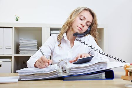 hectic: Busy business woman on the phone taking notes and using a calculator