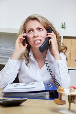 Angry business woman in her office on two phones at the same time photo
