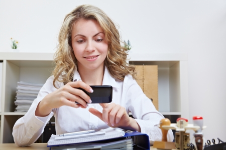 Business woman with smartphone in office using the touchscreen photo