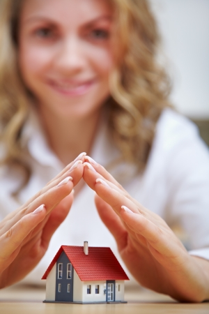 buy house: Smiling woman holding her hands protectively over a small house