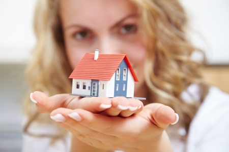 Blonde woman carrying a small house on her hands photo