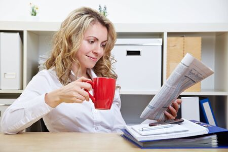 Smiling business woman in her office reading newspaper while drinking coffee