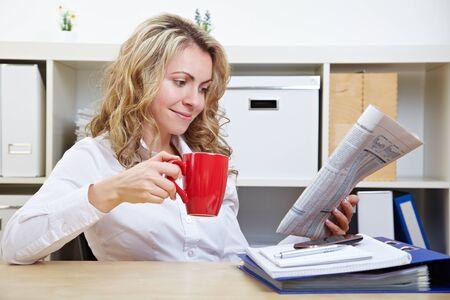 Sourire femme d'affaires dans son bureau tout en lisant le journal de boire du caf�