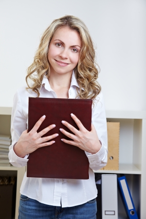 Happy blonde woman standing with application portfolio in the office photo