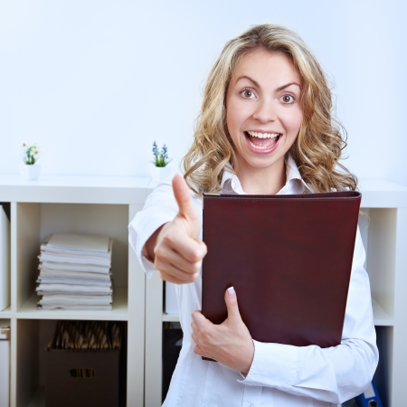 Female happy job candidate with CV holding her thumbs up photo