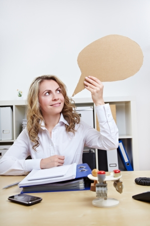 Attractive blonde woman holding empty speech balloon in the office photo