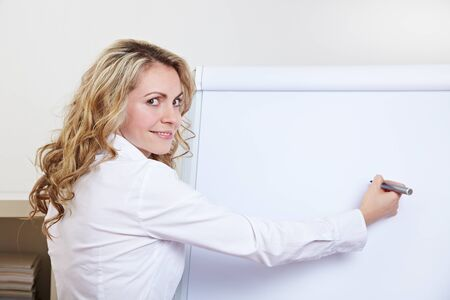 Business woman in her office writing with a pen on a flipchart Stock Photo - 14736680