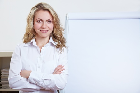 business pitch: Happy blonde business woman standing in front of a flipchart
