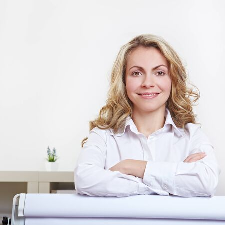 Attractive blonde business woman standing behind flipchart with her arms crossed photo