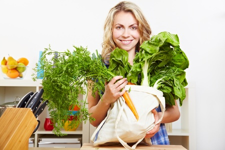 fabric bag: Happy attractive woman standing in kitchen with vegetables in shopping bag Stock Photo