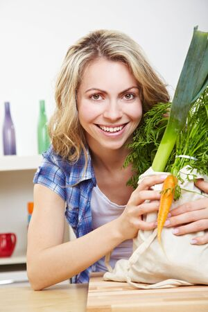 Happy young woman with a shopping bag full of vegetables in the kitchen Stock Photo - 14754572