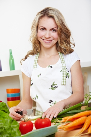 Happy young woman cutting different vegetables in the kitchen Stock Photo - 14754734