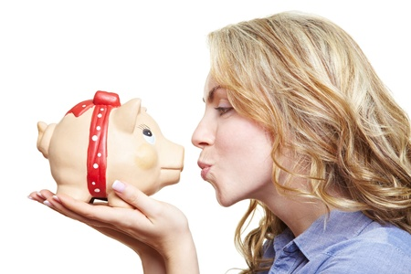 Attractive blonde woman kissing piggy bank on her hands photo