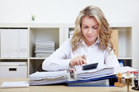 administracion de empresas: Mujer de negocios, el cálculo de la factura en su oficina en el escritorio Foto de archivo
