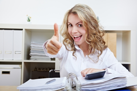 examiner: Happy business woman in office with files holding thumbs up