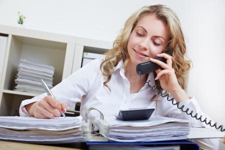 llamando: Atractiva mujer de negocios haciendo una llamada telefónica en su oficina Foto de archivo