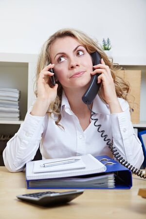 Stressed business woman in the office using two phones simultaneously photo
