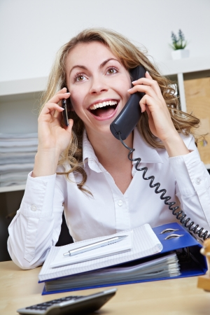 Smiling happy business woman making calls with two phones in her office photo