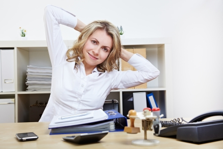 doing business: Happy business woman doing back exercises at work in her office Stock Photo