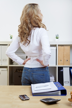 Business woman with back pain standing in her office photo