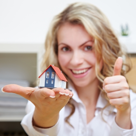 Realtor: Smiling blonde woman with little house holding her thumbs up Stock Photo