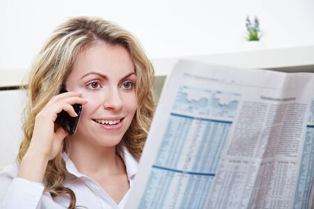job satisfaction: Attractive young woman using her phone while reading the newspaper Stock Photo