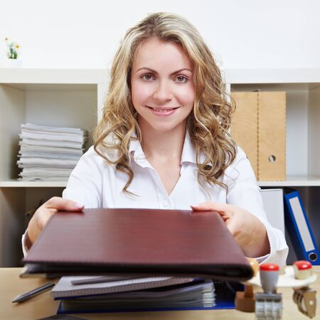 Smiling blonde woman in office offering her application material photo