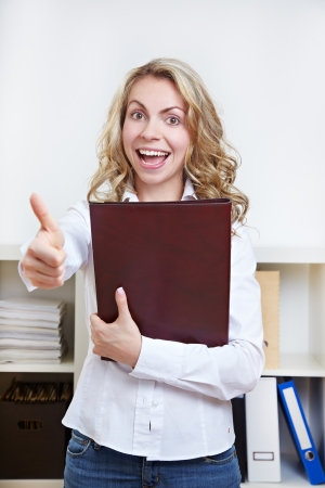 Cheering happy woman with her CV holding her thumbs up photo