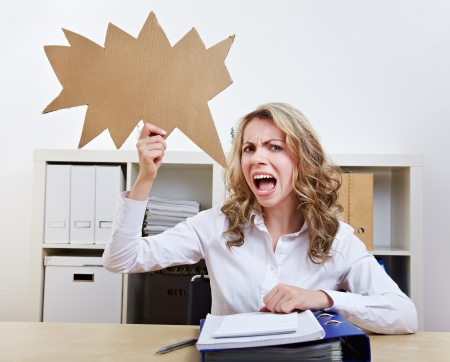Angry woman sitting with empty jagged speech balloon in her office Stock Photo - 14754568