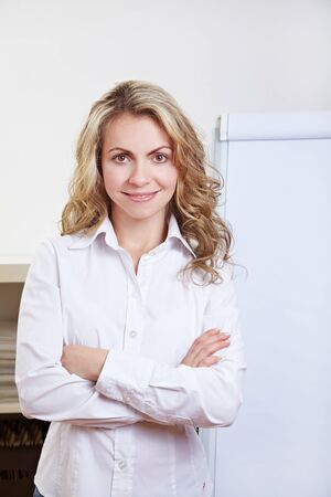 cross arms: Blonde attractive business woman standing in front of flipchart with arms crossed
