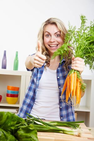 Young happy woman with vegetables in kitchen holding her thumbs up photo