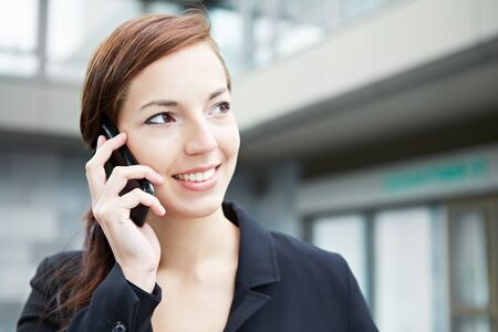 servicing: Business woman on the smartphone in a city Stock Photo