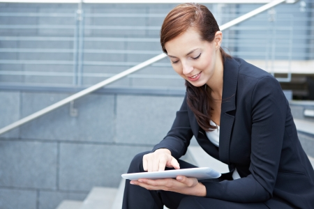 Urban business woman sitting with tablet computer on stairs photo